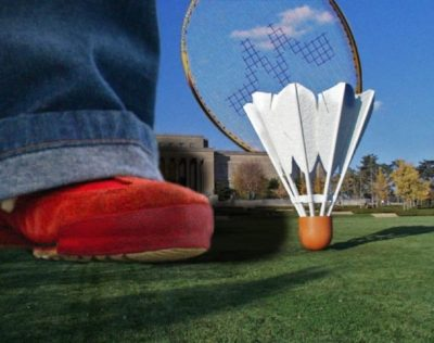 Photo of a giant shoe next to a badminton shuttlecock and racket. There is a building in the background.